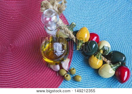multicolored background with mediterranean food olive oil garlic and pepper on handicrafts place mat