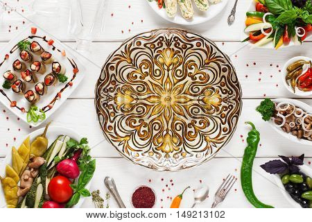 Beautiful ethnic plate in center of food, void, flat lay. Dish with golden mandala ornament surrounded of vegetarian snacks, free space