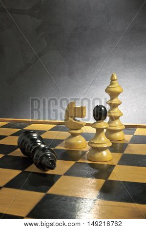 Chess game comes to an end over a grunge background. The king is checkmated.