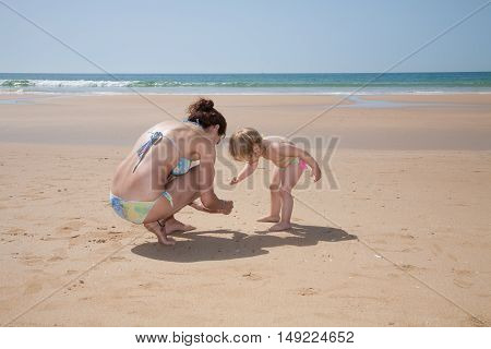 Woman And Baby Collecting Sea Shells