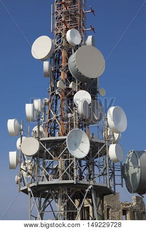 Telecommunication mast iron tower with group of parabolic antennas