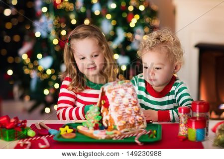 Little boy and girl making Christmas gingerbread house at fireplace in decorated living room. Kids playing with ginger bread under Christmas tree. Baking and cooking with children for Xmas at home.