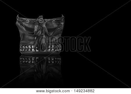 chic or luxury leather black bag with diamond studs, fringe tuft and sling strap for women on black background and reflection shadow isolated included clipping path