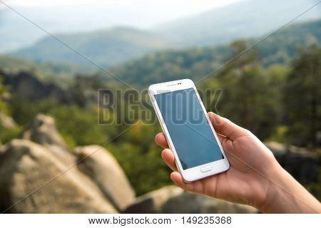 Closeup of a woman's hand is holding mobile phone.