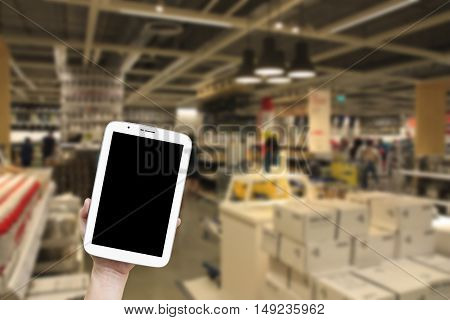 people holding and looking black screen display on tablet for online shopping and sales or find business data on blur shopping mall background