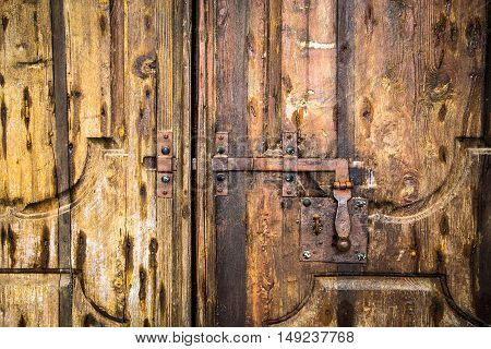 Iron rusty deadbolt on old wooden door.