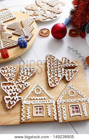 Decorated christmas gingerbread cookies and edcorations on the table.
