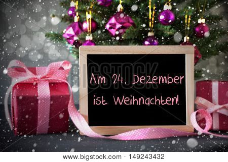 Chalkboard With German Text Am 24. Dezember Ist Weihnachten Means December 24th Is Christmas Eve. Tree With Rose Quartz Balls, Snowflakes And Bokeh Effect. Gifts In Front Of Cement Background.