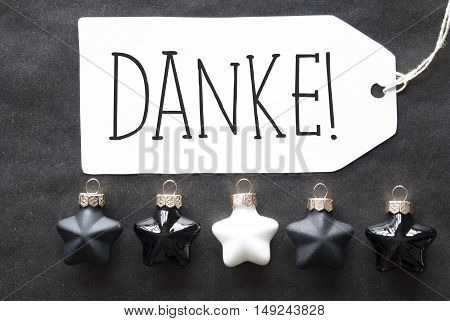 Label With German Text Danke Means Thank You. Black And White Christmas Tree Balls On Black Paper Background. Christmas Decoration Or Texture. Flat Lay View