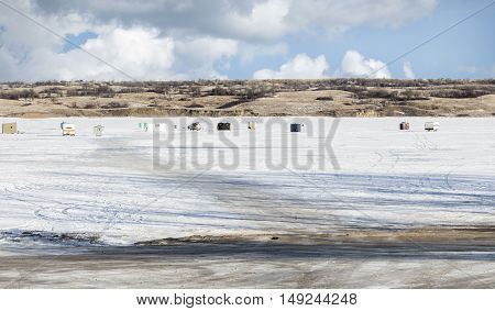 horizontal image of many ice fishing huts sitting on a white snow covered lake under a bright blue sky with clouds on a cold winter day.