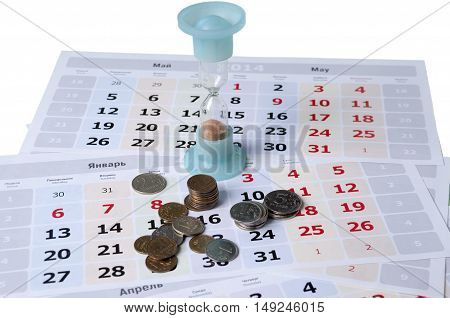 Hourglass standing on calendar leaves and some small coins