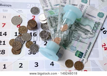 Rubles are scattered on the calendar and hourglass