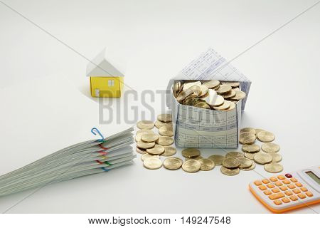 House of gold coins and pile overload document of report with colorful paperclip with calculator and little house have blur on white background.