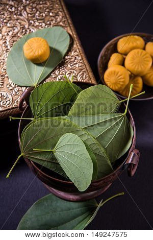 indian festival dussehra or vijayadashmi or ayudh puja, showing apta leaf or Bauhinia racemosa with traditional indian sweets pedha in silver bowl poster