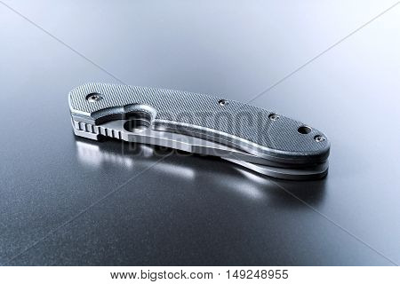 Handle Of A Lying Military Knife Lying On Dark Ground With Reflection