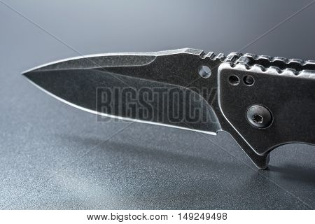 Macro Of A Blade Of An Opened Black Folding Knife Which Stands On Dark Ground