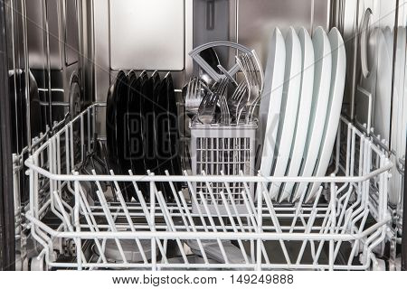 Clean dishes after washing in modern dishwasher machine poster