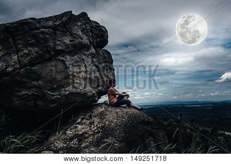 Woman Sitting On Boulders, Sky With Cloudy And Full Moon. Low Key And High Contrast Style.