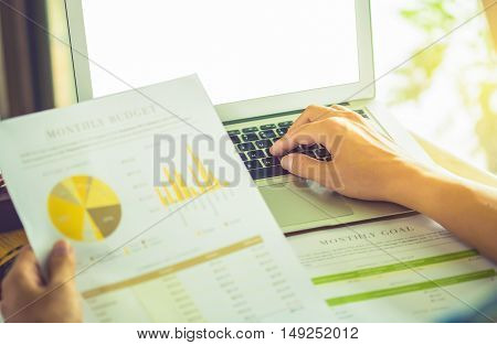 close up Business man using laptop witch holding stock maket chart on wood desk in office. vintage effect.