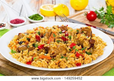 paella with meat pepper vegetables and spices on dish on cutting board lemon slice spices and cherry tomatoes on background view from above close-up