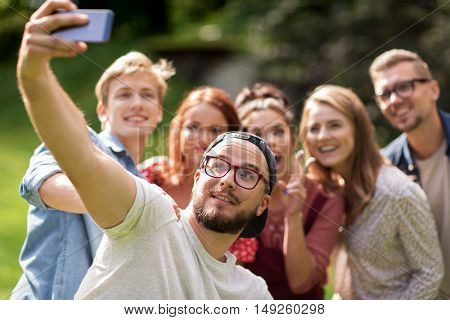 leisure, holidays, reunion, people and friendship concept - happy teenage friends taking selfie by smartphone at summer