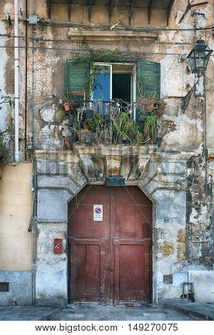 vintage balcony with different flowers, cracked plaster and wooden doors, Mediterranean style on island Sicily, Italy