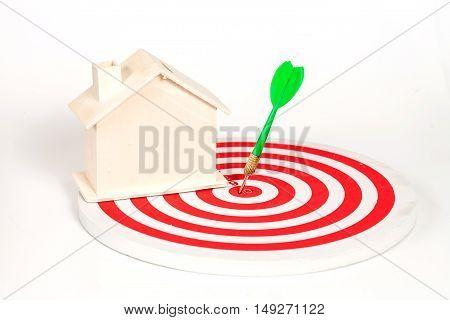 Miniature house on dart board white background