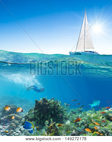 Catamaran and young woman snorkling underwater with fish and corals