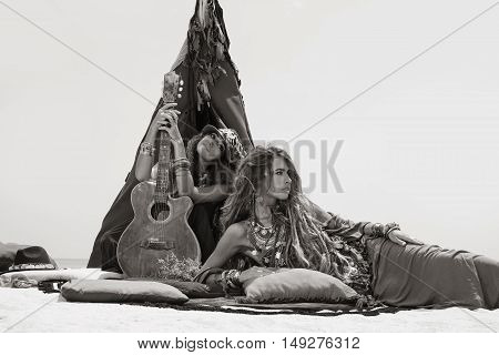Two Beautiful Gypsy Girls With Guitar Sitting On Pillows At Tepee