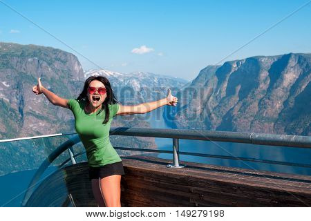 Excited woman tourist at Stegastein Viewpoint in a summer sunny day showing thumb up gesture, Flam, Norway