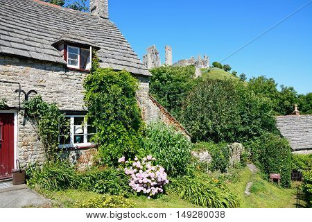 CORFE, UNITED KINGDOM - JULY 19, 2016 - Pretty stone cottage with the castle to the rear Corfe Dorset England UK Western Europe, July 19, 2016.