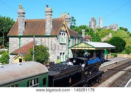 CORFE, UNITED KINGDOM - JULY 19, 2016 - LSWR T9 Class 4-4-0 steam train entering the railway station with the castle to the rear Corfe Dorset England UK Western Europe, July 19, 2016.