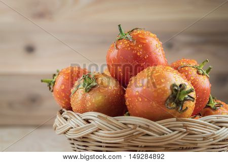 tomatoes in basket on wooden table. tomatoes fresh. tomatoes on wood background. tomatoes food. tomatoes orange. tomatoes eating. tomatoes background. tomatoes from Thaialnd.