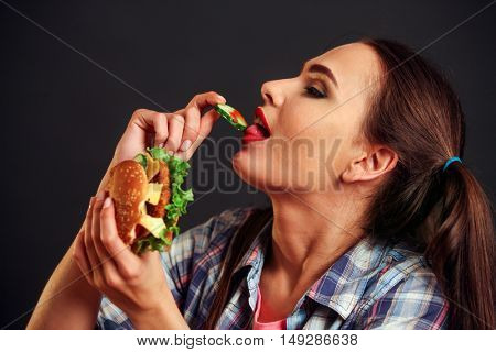 Girl eating hamburger with appetite . Girl biting small piece of hamburger.