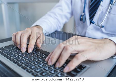 Close-up of a medical worker typing on laptop. Doctor man. Doctor woman. Doctor using laptop. Doctor using notebook. Doctor using computer.