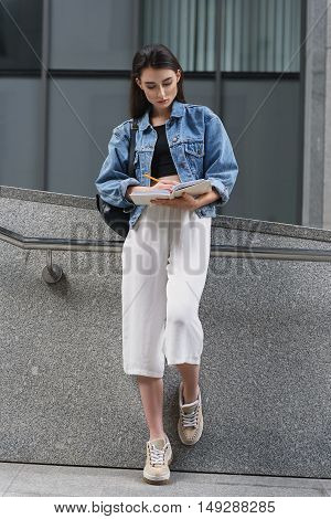 Full length of woman outdoors who writing in her notebook