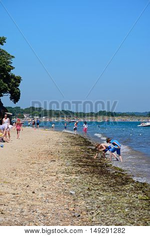 STUDLAND BAY, UNITED KINGDOM - JULY 19, 2016 - View along the beach with holidaymakers enjoying the Summer sunshine Studland Bay Dorset England UK Western Europe, July 19, 2016.