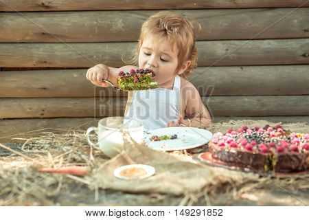 Cute little boy in white pinafore eats fruit cake and cup of milk at table outdoors on wooden background