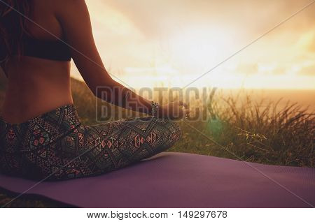 Female Sitting In Lotus Yoga Pose On Exercise Mat