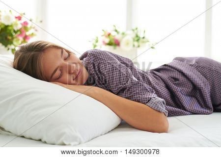 Close-up of beautiful woman in satin pajamas sleeping peacefully on white pillow in light cozy bedroom