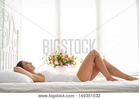 Happy young woman with a well set-up figure enjoying sunny morning in the bed, she dressed in a white nightgown wakes up in the morning on a soft pillow in a white bed in bright bedroom