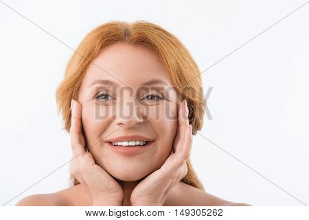 Beautiful middle-aged woman is touching her smooth face with pleasure. She is standing and smiling happily. Isolated