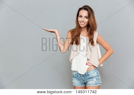 Cheerful attractive young woman standing and holding copyspace on palm over grey background