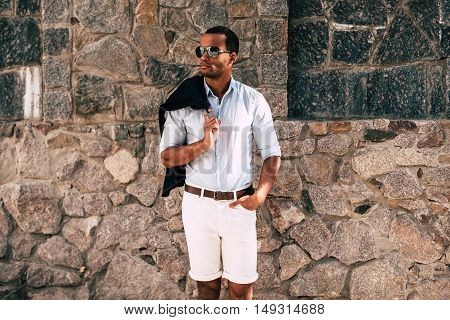 Stylish handsome. Handsome young African man in smart casual clothes carrying jacket on shoulder and looking away standing against the stoned wall outdoors