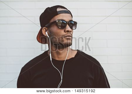 Music is his life. Handsome young African man in headphones looking away and looking serious while standing in front of the stoned wall outdoors