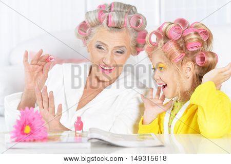 Senior woman and granddaughter painting nails at home