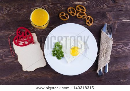 Fried egg for breakfast. Breakfast with a wish for the beloved. Good morning my love. Freshly squeezed juice eggs and a heart-shaped card.