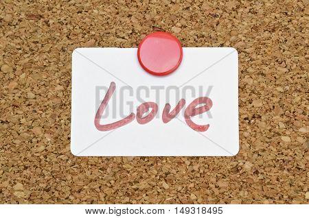 Word Love written on a sticker pinned on a cork board