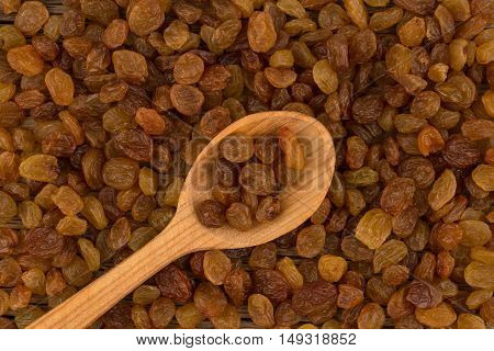 Raisins in wooden spoon and background of raisins. Top view.