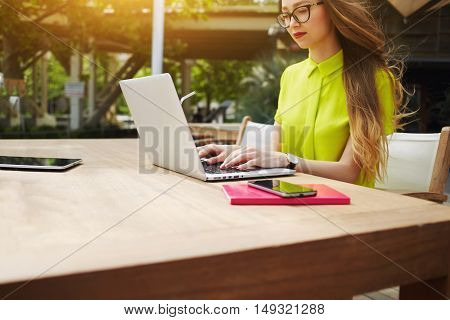 Young woman manager is working on laptop computer while is sitting in cafe before interview with new employees. Pretty female student is keyboarding text message while studying via portable net-book